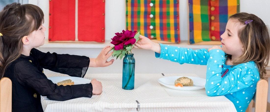 Holčičky s květinou u stolu