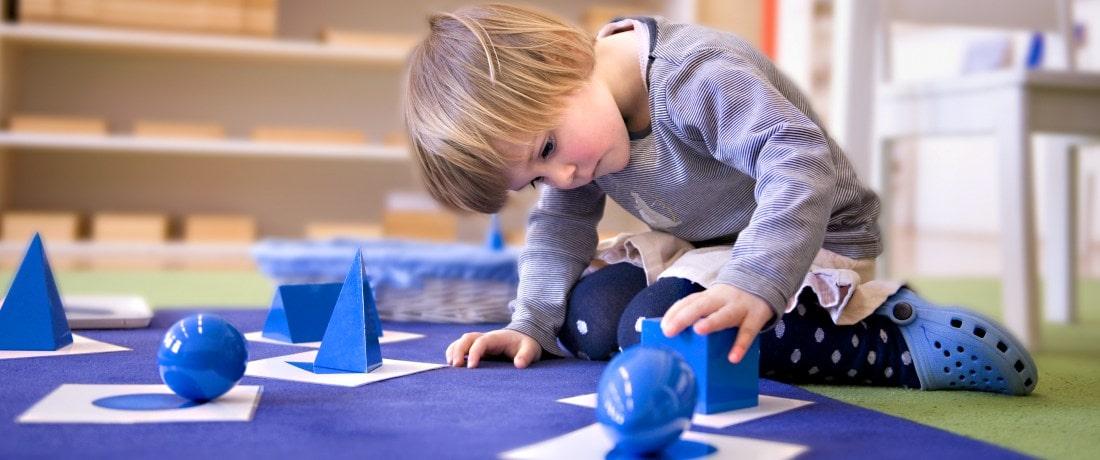 Holčička hrající se součástkami různých tvarů
